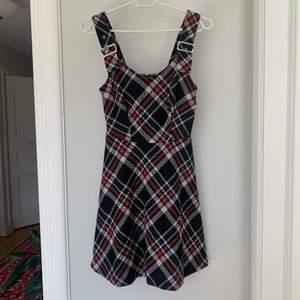 Fin, rutig klänning i a-line-modell med metallspännen på axelbanden