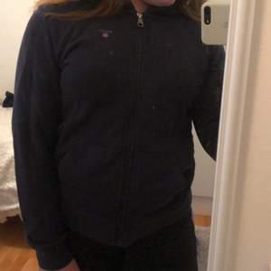 En mörkblå hoodie med en dragkedja och två små fickor, från gant. Finns luva (bild 2) Storlek 170💕           Köpare står för frakt!