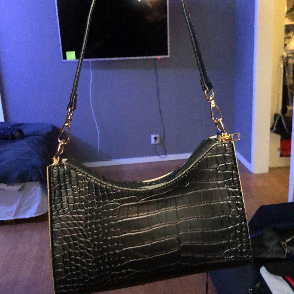 En svart axelväska med gumdetaljer! En väldigt populär väska som jag inte använder. Säljs pga att den används 1 gång. Väskor.