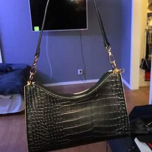 En svart axelväska med gumdetaljer! En väldigt populär väska som jag inte använder. Säljs pga att den används 1 gång