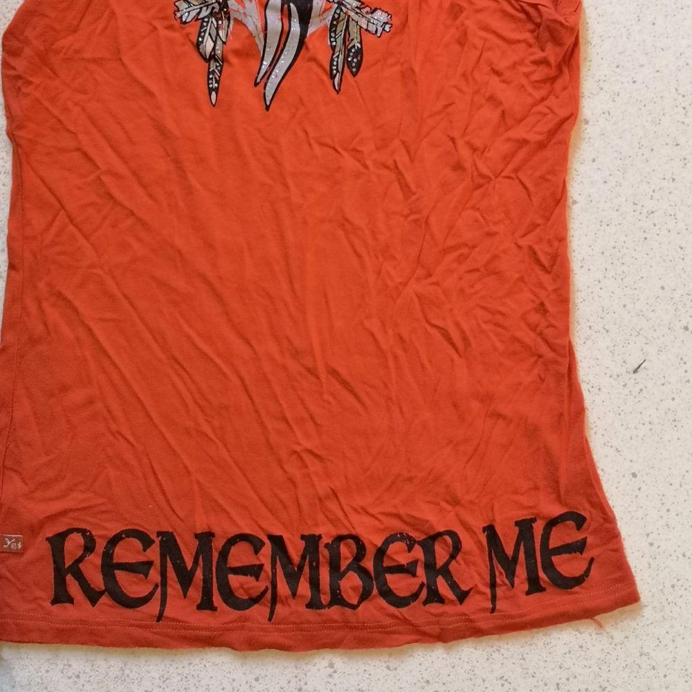 Tufft linne med fjädrar och texten Remember Me på baksidan. Köpt utomlands, använd enstaka gång. Sitter fint i kroppen i ett tunt tyg. . Toppar.