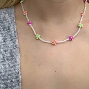 Vitt pärlhalsband med små pärlor och söta blommor i olika färger 🤍💞🦋💚💜 halsbandet försluts med lås och tråden är elastisk