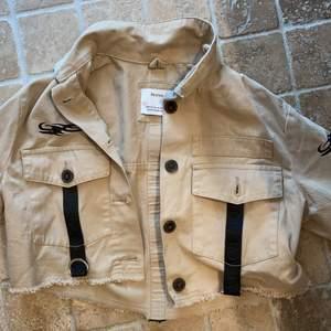 beige croppad jeansjacka med supercoola detaljer! har två fickor. bra skick.