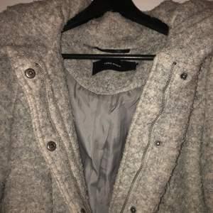 En grå kappa från veromoda. Köpt för 1999kr men säljer för 700kr. Kappan ger ner till början av knäna. Tjock material med stor luva. Funkar att knäppa med dragkedja och knappar. Finns två stora fickor.