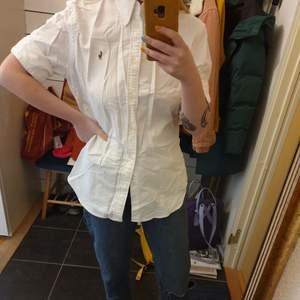 Vit kortärmad skjorta från Ralph Lauren. Är fin till jeans. Man kan välja om man vill vika upp manchetterna eller inte för en kortare ärm. Skjortan kommer strykas innan den skickas.