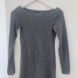 Långärmad ljusgrå långärmad tröja med mörkgrå ränder från Gina tricot , stretchigt och mjukt material. Storlek ca men funkar även på S för en figurnära passform. tröjan är i mycket gott skick.