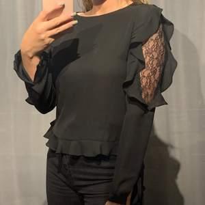 En jätte fin svart blus från Zara som är broderad på överarmen och volanger runt om. Knappt längs ryggen och volanger längs nere runt om blusen. Jätte fin blus. Storlek S. Skriv gärna i PM om eget prisförslag