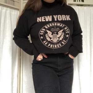 Supercoool svart collegetröja i croppad model med ett New York tryck!🗽Väldigt fint skick, jättebra kvalité och supermysig! Overzised och därför passar den både S-L beroende på hur man vill den ska sitta. Köpt i New York. Köparen står för frakten🖤