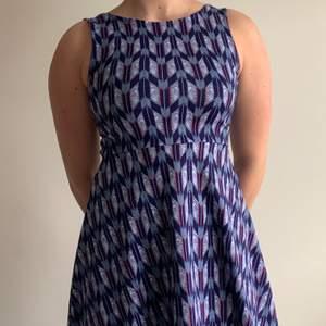 En härlig sommarklänning med fint mönster, marinblå med ljusblåa och orangea detaljer. Kort klänning, djup i ryggen i storlek 38, är något liten i storleken.