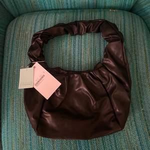 Superfin oanvänd svart liten väska från MONKI