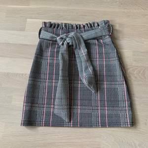 Kort rutig kjol med snyggt reglerbart knytskärp från Boohoo. Nyskick, använd en gång.