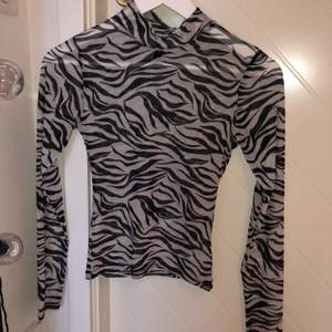 En tajt långärmad tröja med lite högre krage i zebramönster. Tröjan är från H&M i storlek XS och är sann till storleken och i väldigt bra skick, näst intill oanvänd. Köparen står för frakten, men kan i vissa fall mötas upp i Stockholm.