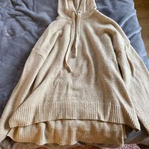Beige stickad tröja med luva från H&M. Den är 63% akryl, 32% polyamid och 5% ull