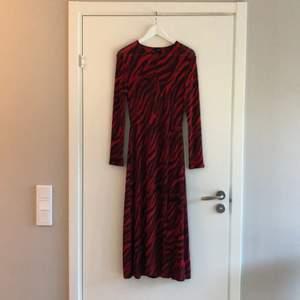Röd och svart klänning i zebramönster! Tight modell som går ut nertill. Använd 1 gång.