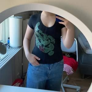 urringad svart t-shirt med ett grönt coolt tryck på framsidan!! säljer då den är för liten i armarna på mig ☺️☺️