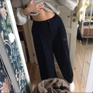 Kostymbyxor i flanell vilket verkligen gör dem extremt bekväma, som flanellpyjamas byxor. Mörkt marinblå med vita kritstrecksränder. Köpta för 679kr och använda 1 gång. Modellen heter odina trousers.