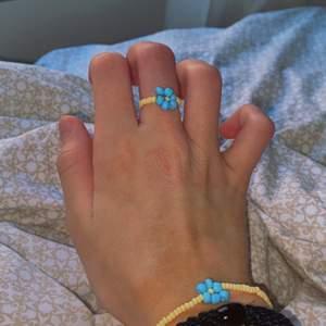 """NEW IN! Nu har jag nya handgjorda smycken!! Detta är ett """"sätt"""" som du kan köpa tillsammans eller t.ex. bara ringen eller bara armbandet! Armbandet har tre blåa blommor på sig med en karbinhake. Ringen har en blå blomma fäst med knut som inte syns! (Sättet kan göras i lila också om önskas)🤎 skriv till mig om ni vill veta vad ringen kostar och vad armbandet kostar! (Blir billigare om man köper det som ett sätt dvs köper dem tsm) köparen står för frakt!🚚"""