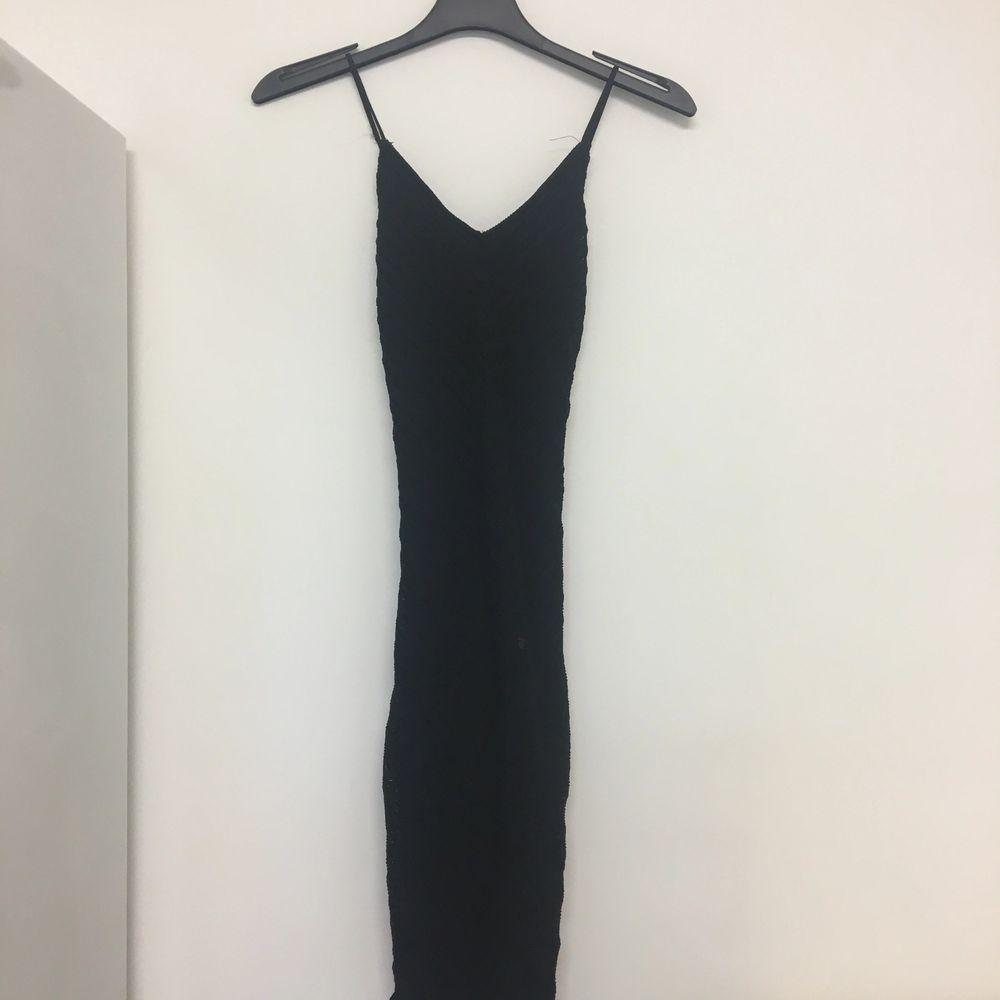 Svart klänning med textur. Sitter tight och är lagom lång. (Ej så lång som den ser ut på bilden) Korsade band över ryggen. Passar XS och S.. Klänningar.