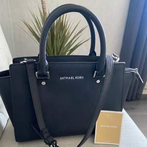 Säljer min Michael Kors väska i modellen Selma, då jag inte fått mycket användning av den. Använd bara ett fåtal gånger så är i ett väldigt bra skick. Repor finns endas på nitarna på undersidan. (Helt äkta och köpt i Sverige)