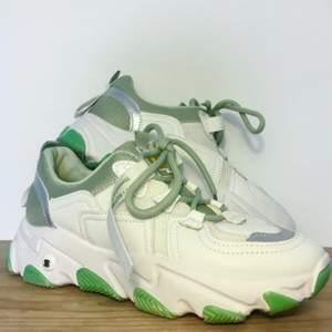 Supersnygga trendiga vita sneakers med gröna detaljer (mintgrönt foder och snören, grön sula). Strl 38. Endast använda en gång, riktigt bra skick :)