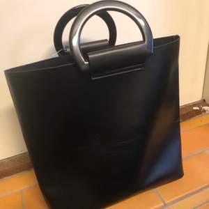 """Svart oanvänd väska i läderimitation med snygga runda handtag i plast. Superfin och """"modern""""."""