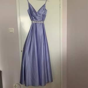 Intressekoll på balklänning. Lavendel lila färg med tjockt sidenliknande material. Lång och har slit i höger ben. Bälte medföljer och är avtagbart. Fint skick bara använt en gång!