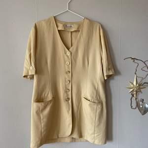 En second hand köpt gul kortärmad skjorta tröja med V-ringning och gula knappar.