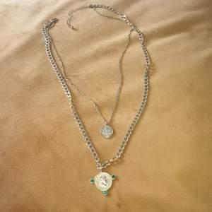 Två halsband som spännes i ett och samma, guldimitation.