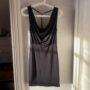 Svart åtsittande klänning med silverdetalj i ryggen. Storlek XS från NLY ONE