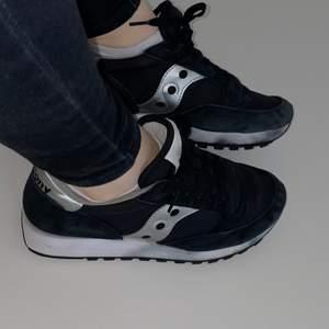 Svarta Saucony skor. Vid tvätt har det svarta tyvärr färgat av sig på sulorna, där av är priset lågt.