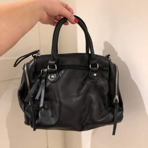 Svart handväska från HM. Köpte för några år sedan men är i väldigt bra skick då jag sällan använde den. Hade ett längre band innan som var avtagbar, men den har jag tappat bort. FRAKT: 80kr