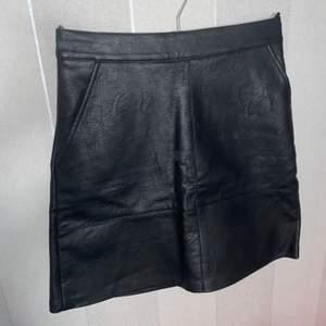 Högmidjad, svart kjol i läderimitation ifrån Only. En silvrig dragkedja i bak samt fickor på framsidan. Endast använd 1 gång! Strl. 34