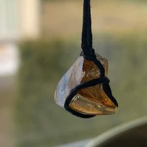 Hemmagjort halsband med en krossad guldig sten, svart tygband som är ungefär 47 cm lång, skriv gärna om ni har några tips eller frågor också <3 Finns en till som ser likadan ut fast kortare snöre, 37cm.