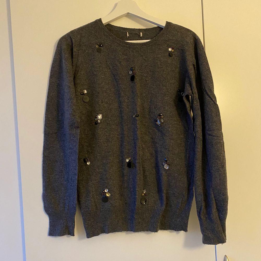 Snygg grå tröja med stenar. Mjuk och varm. Använd men i bra skick. Material är ullmix. Finns inte storlek lappar men ungefär S-M.. Stickat.