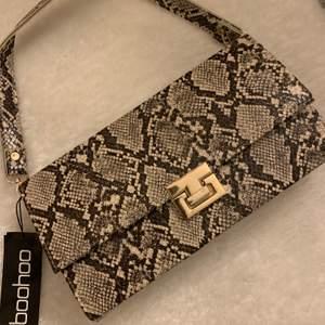 Handväska med ormskinnsmönster och dekorativt lås Från boohoo, använt nån gång.  ~(Köpare står för frakten)~