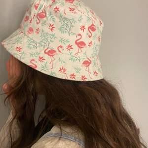 En hatt med flamingosar på, aldrig använd, bra skick, säljer för minst 50 men högsta bud vinner, köparen står för frakt