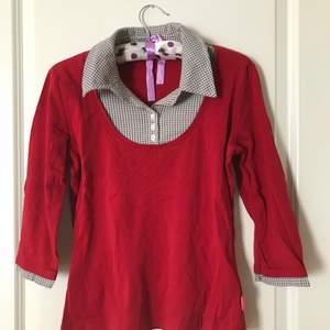 A red shirt of cotton, makes it look like a double. Very comfortable, 3/4 sleeve. Köparen står för frakten.
