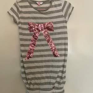 Gullig och fin tröja med en rosa rosett på! Strl 152 men sitter som en S💕
