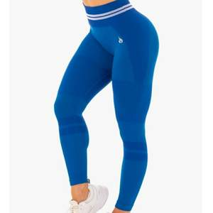 Blå Ryderwear träningstights  Namn: The free Seamless high waist leggings Väldigt bra skick. Endast använd två gånger Storlek Small S Nypris är ca 749 kr Samfraktar  Detta är hemsidans förklaring:  The Freestyle Seamless High Waist Leggings have been perfected for optimal movement, constructed from our unrivalled seamless knit technology for that near naked feel. Whether you're lounging or lunging, these leggings offer ultimate comfort with a fun, fashionable, body contoured style. The distinctive love heart booty and ribbed contouring flatter your figure, flaunting your glutes and waist. The seamless fabric provides maximum range of motion and agility for dynamic, high-octane home workouts. These luxe leggings also feature a stylish, woven athletic double stripe and can be paired perfectly with the Freestyle Longline Sports Bra.  -High waisted legging  -Full length  -Seamless knit technology  -Smooth second skin fit  -Supportive seamless rib waistband  -Flexibility for maximum movement  -Lightweight  -Woven Ryderwear logo  Recommended for lifestyle, home workouts and gym training.  Due to the nature of the soft, seamless fabric we recommend to always wear similar skin tone seamless G-Strings under your seamless leggings and shorts.  Model is 167cm tall, she usually wears a size Small and is wearing a size Small. Her waist measures 69cm and her hips measure 84cm.  63% Nylon/24% Polyester/13% Spandex