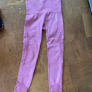 """Rosa gymshark-tights med """"håldetaljer"""" som säljs eftersom jag köpte de av misstag. Nyskick utan skavanker, färgen är mer rosa (ej lila) än vad som framgår på bilderna. Möts i Stockholm eller fraktar mot tilläggskostnad."""