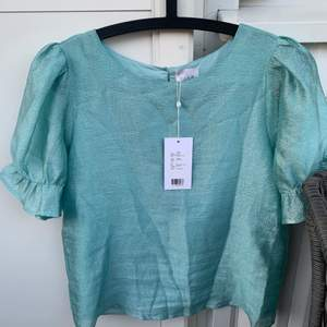 Ny helt oanvänd VILA blus i blå/grön, köptes häromdagen. Jättefin och bra kvalité med puffärm. Frakt betalas av köparen!