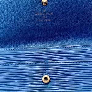 Louis Vuitton Epi läder long wallet  Fin plånbok tillverkad i Louis Vuittons Epi läder. Guldfärgade metalldetaljer. Flera fack invändigt anpassade både för sedlar, mynt och kort.  Det s k Epi lädret introducerades 1985 av Louis Vuitton i syfte att skapa ett hållbart men lyxigt material.  Detaljfakta:   Tillverkningsland: Spanien  Datumkod/Serienummer: CA0996  Mått: 19 x 10 cm  Färg: Blå  Material: Epi läder  Varans skick:   I bra vintage begagnat skick. Ställvis slitage.