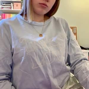 """En ljusblå sweatshirt från H&M i storlek M. Tröjan har tryckt vit text på där det står """"Tokyo love"""", som dock flagnat bort lite."""