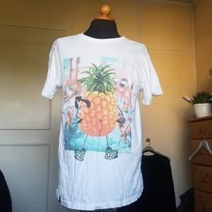Denna t-shirt med ett tryck av en ananas med glasögon, skor och en bar rumpa säljes då den blev använd en gång och sedan dess legat i garderoben. Rätt oversize men rolig. Från tshirtstore. Passar alla.