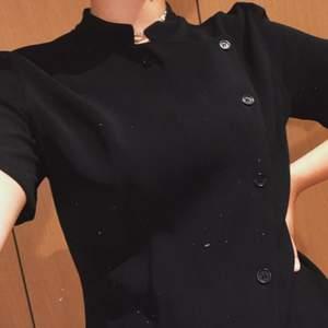 Superfin svart retro/vintage Emporio Armani topp i kostym-aktigt tyg med knappar. Kragen är kort (råkade vara lite vikt på bilden) och ärmarna slutar över armbågarna. Tröjan stängs med knappar och ligger omlott/snett över bysten. 🧚🏼🧚🏼 FRAKT INGÅR I PRISET! 📦