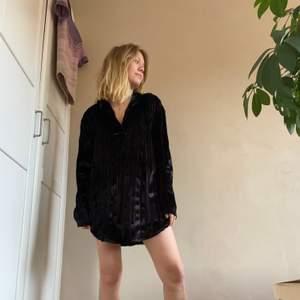 Säljer denna snygga velour-klänning i svart med djup v-ringning och krage. Den är så blank och skiner så den upplevs glittrig. Hänger sjukt snyggt på kroppen och är i fint skick. Passar både med som utan något i midjan och har själv både använt med något under samt utan. En perfekt party-blåsa!