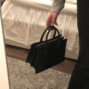 Superfin svart väska. Den har två större fack och ett mindre med dragkedja. Ett längre band medföljer. Använd typ en gång så helt som ny.