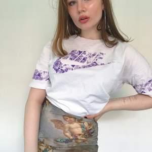 Vit Oversized Nike T-shirt mes super gulligt lila blomster print på loggan och ärmarna. Super fin till sommaren tucked in i jeanshorts eller som lång oversized T-shirt. Storlek M men snygg som oversize på mindre storlekar.