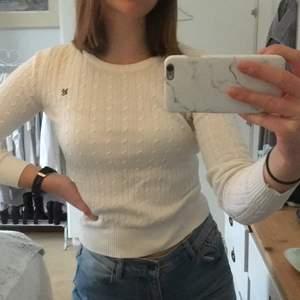 Vit stickad tröja, med detalj på vänster bröst