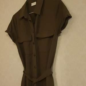 Olivgrön, viskos- och nylontygn, stl.34, 2 bröstfickor, rak i modellen, uppvikta ärmfållar, vadlång, med midjeband, knappt använd